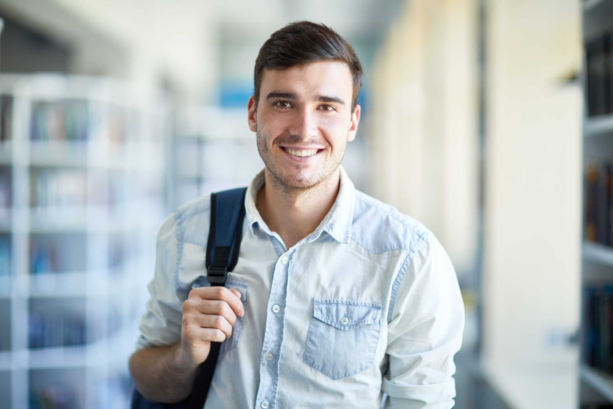 Smiling handsome young guy in denim shirt holding handle of satchel and looking at camera while standing in university corridor