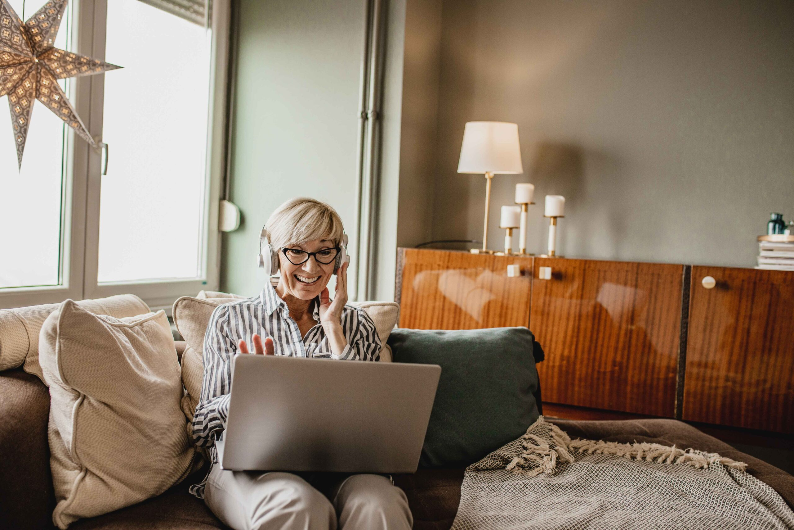 Mature woman is in her modern apartment using a laptop